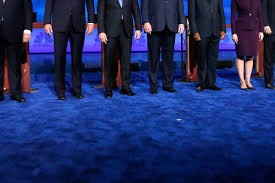 The one in heels is Marco Rubio. The one with the Larry Craig wide stance is Ted Cruz.